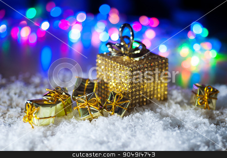 Christmas present in gold wrapping with ribbon on winter background stock photo, Christmas present in gold wrapping with ribbon on winter background. by timonko