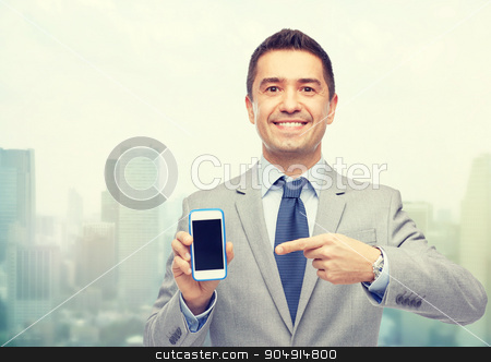 happy businessman showing smartphone screen stock photo, business, people and technology concept - happy smiling businessman in suit showing smartphone black blank screen over city background by Syda Productions