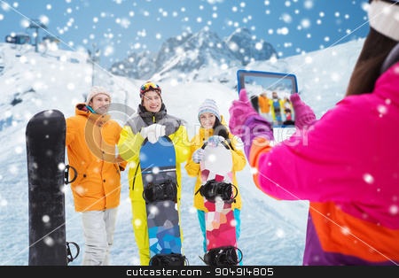 happy friends with snowboards and tablet pc stock photo, winter sport, technology, leisure, friendship and people concept - happy friends with snowboards and tablet pc computer taking picture over snow and mountain background by Syda Productions
