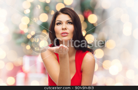woman sending blow kiss  over christmas lights stock photo, christmas, people, holidays and gesture concept - beautiful sexy woman in red dress sending blow  kiss over holidays lights background by Syda Productions