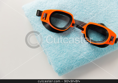 close up of swimming goggles and towel stock photo, sport, fitness, water sports and objects concept - close up of swimming goggles and towel by Syda Productions