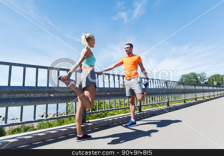 smiling couple stretching outdoors stock photo, fitness, sport, training and lifestyle concept - smiling couple stretching outdoors by Syda Productions