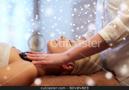 close up of woman having hot stone massage in spa stock photo, people, beauty, spa, healthy lifestyle and relaxation concept - close up of beautiful young woman having hot stone massage in spa with snow effect by Syda Productions