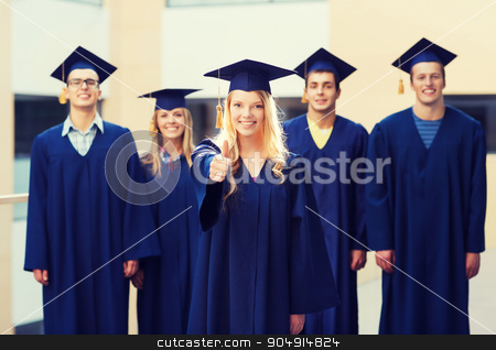 group of smiling students in mortarboards stock photo, education, graduation, gesture and people concept - group of smiling students in mortarboards and gowns showing thumbs up outdoors by Syda Productions