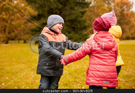 children holding hands and playing in autumn park stock photo, childhood, leisure, friendship and people concept - group of happy children holding hands and playing in autumn park by Syda Productions