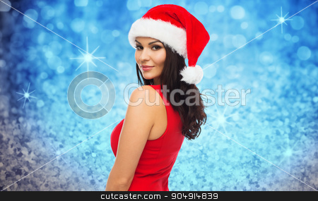 beautiful sexy woman in santa hat and red dress stock photo, people, holidays, christmas and celebration concept - beautiful sexy woman in santa hat and red dress over blue glitter and lights background by Syda Productions