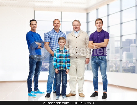 group of smiling men and boy stock photo, real estate, gender, generation and people concept - group of smiling men and boy over empty apartment or office room background by Syda Productions