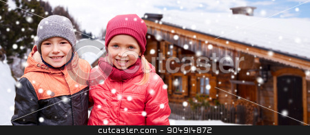 happy girl hugging boy over country house and snow stock photo, childhood, winter holidays, christmas, friendship and people concept - happy little girl and boy over wooden country house and snow background by Syda Productions
