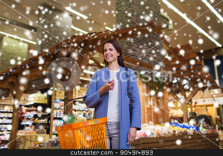 happy young woman with food basket in market stock photo, sale, shopping, consumerism and people concept - happy young woman with food basket in grocery store or market over snow effect by Syda Productions