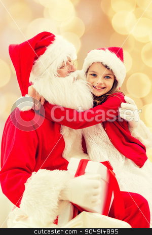 smiling little girl with santa claus stock photo, holidays, christmas, childhood and people concept - smiling little girl hugging with santa claus over beige lights background by Syda Productions