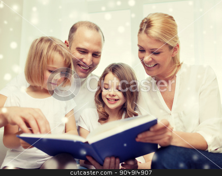 happy family with book at home stock photo, family, leisure, education and people - smiling mother, father and little girls reading book over snowflakes background by Syda Productions