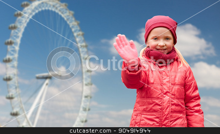 happy little girl waving hand over ferry wheel stock photo, autumn, childhood, gesture, nature and people concept - happy little girl waving hand over london ferry wheel and blue sky background by Syda Productions