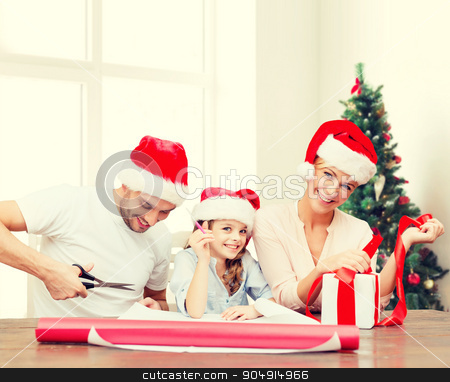 happy family in santa helper hats packing gift stock photo, holidays, family and people concept - happy mother, father and little girl in santa helper hats with gift box and scissors over living room and christmas tree background by Syda Productions