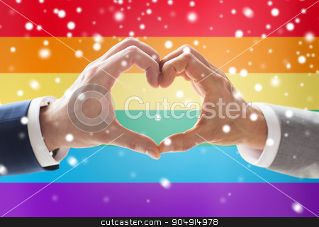close up of male gay couple hands showing heart stock photo, people, homosexuality, same-sex marriage, gesture and love concept - close up of happy male gay couple hands showing heart hand sign over rainbow flag background and snow effect by Syda Productions