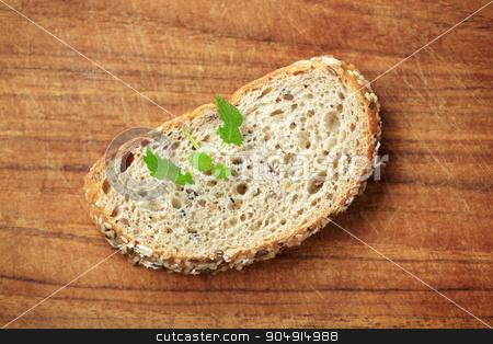 Slice of whole grain bread stock photo, Slice of whole grain bread on a cutting board by Digifoodstock
