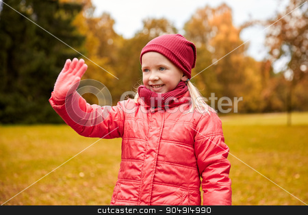 happy little girl waving hand in autumn park stock photo, autumn, childhood, gesture, nature and people concept - happy little girl waving hand in park by Syda Productions
