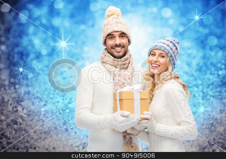 smiling couple in winter clothes with gift box stock photo, winter, holidays, couple, christmas and people concept - smiling man and woman in hats and scarf with gift box over blue glitter and holidays lights background by Syda Productions