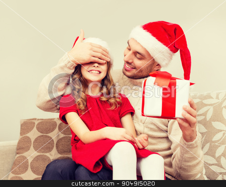 smiling father surprises daughter with gift box stock photo, family, christmas, x-mas, happiness and people concept - smiling father surprise daughter with gift box covering eyes with hand by Syda Productions