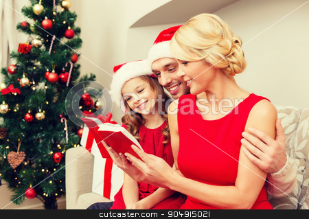 smiling family reading book stock photo, family, christmas, x-mas, happiness and people concept - smiling family in santa helper hats with many gift boxes reading book by Syda Productions