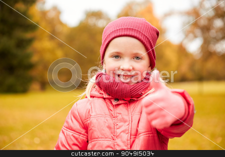 happy little girl showing thumbs up in autumn park stock photo, autumn, childhood, nature and people concept - happy little girl showing thumbs up in park by Syda Productions