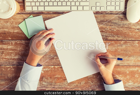 close up of hands with paper sheet and keyboard stock photo, business, education, technology and people concept - close up of female hands with paper sheet, pencil and computer keyboard on table by Syda Productions