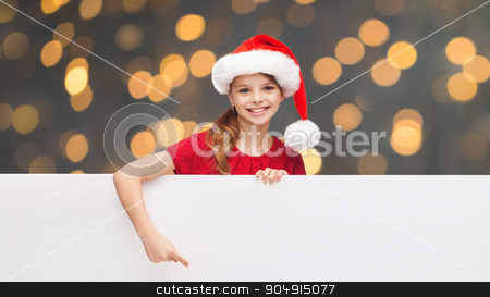 child in santa helper hat with blank white board stock photo, christmas, people, children and advertisement concept - happy girl child in santa helper hat pointing finger on blank white board over golden lights background by Syda Productions