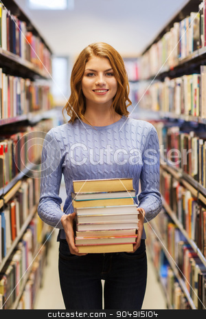 happy student girl or woman with books in library stock photo, people, knowledge, education and school concept - happy student girl or young woman with stack of books in library by Syda Productions