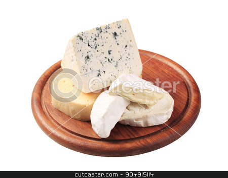 Assorted cheeses stock photo, Selection of cheeses on a cutting board by Digifoodstock