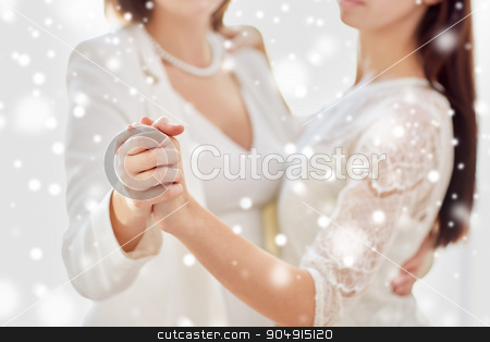 close up of happy married lesbian couple dancing stock photo, people, homosexuality, same-sex marriage and love concept - close up of happy married lesbian couple dancing over snow effect by Syda Productions