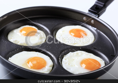 Four fried eggs stock photo, Four fried eggs on a pan - Sunny side up  by Digifoodstock