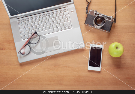 Overhead of modern comfort work place stock photo,  Overhead of modern comfort work place. Different objects on wooden background. Items include camera, glasses, laptop, smartphone and apple by Oleksii