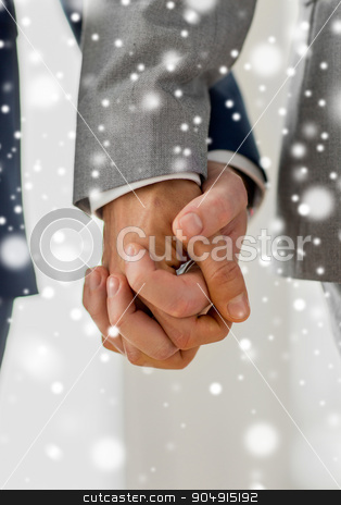 close up of male gay couple holding hands stock photo, people, homosexuality, same-sex marriage and love concept - close up of happy male gay couple holding hands over snow effect by Syda Productions