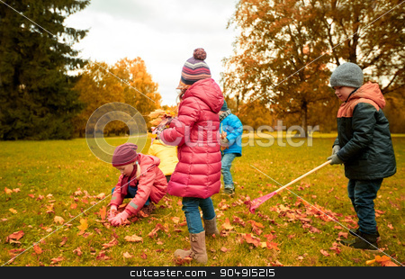 group of children collecting leaves in autumn park stock photo, childhood, leisure, autumn, friendship and people concept - group of children with rack collecting and racking leaves in park by Syda Productions