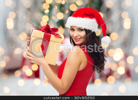 beautiful sexy woman in santa hat with gift box stock photo, people, holidays, christmas and celebration concept - beautiful sexy woman in red dress and santa hat with gift box over christmas tree lights and presents background by Syda Productions