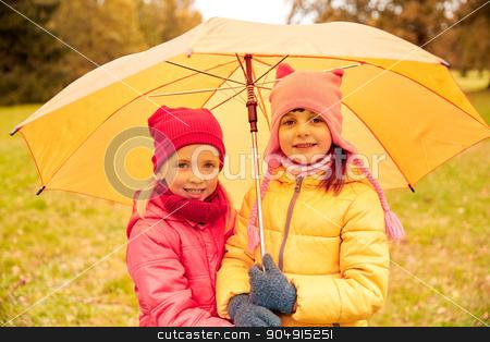 happy little girls with umbrella in autumn park stock photo, childhood, friendship, season, weather and people concept - happy little girls with umbrella in autumn park by Syda Productions