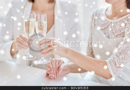 close up of lesbian couple with champagne glasses stock photo, people, homosexuality, same-sex marriage, celebration and love concept - close up of happy married lesbian couple hands holding and clinking champagne glasses over snow effect by Syda Productions
