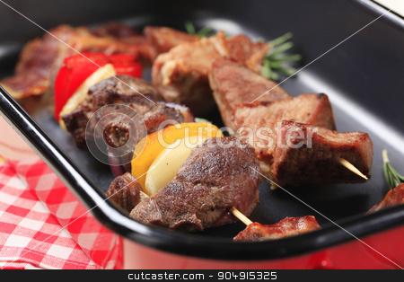 Shish kebabs stock photo, Shish kebabs and rashers of bacon in a roasting pan by Digifoodstock
