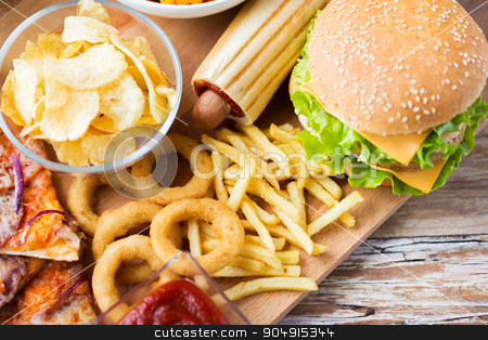 close up of fast food snacks on wooden table stock photo, fast food and unhealthy eating concept - close up of hamburger or cheeseburger, deep-fried squid rings, french fries hotdog and potato chips on wooden table top view by Syda Productions