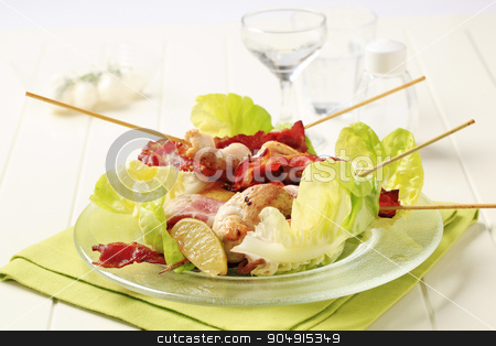 Chicken skewers and crispy bacon stock photo, Chicken skewers and bacon strips served on lettuce leaves by Digifoodstock