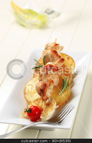 Chicken kebab with slices of pan roasted potato stock photo, Chicken souvlaki on slices of pan roasted potato by Digifoodstock