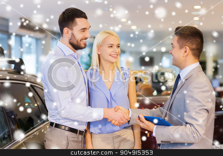 happy couple with car dealer in auto show or salon stock photo, auto business, car sale, technology, gesture and people concept - happy couple with car dealer shaking hands in auto show or salon over snow effect by Syda Productions
