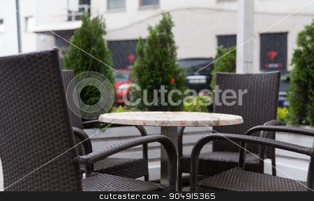 table and chairs on street cafe terrace under rain stock photo, weather, public places and season concept - table and wicker chairs on street cafe terrace under rain by Syda Productions