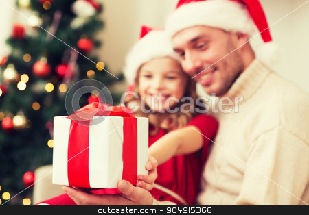close up of father and daughter with gift box stock photo, family, christmas, holidays, happiness and people concept - close up of smiling daughter giving father gift box by Syda Productions