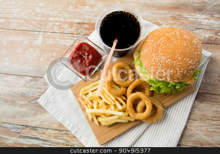 close up of fast food snacks and drink on table stock photo, fast food and unhealthy eating concept - close up of hamburger or cheeseburger, deep-fried squid rings, french fries, cola drink and ketchup on wooden table by Syda Productions