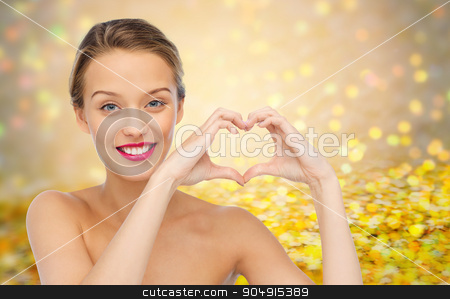 smiling young woman showing heart shape hand sign stock photo, beauty, people, love, valentines day and make up concept - smiling young woman with pink lipstick on lips showing heart shape hand sign over golden glitter or holidays lights background by Syda Productions