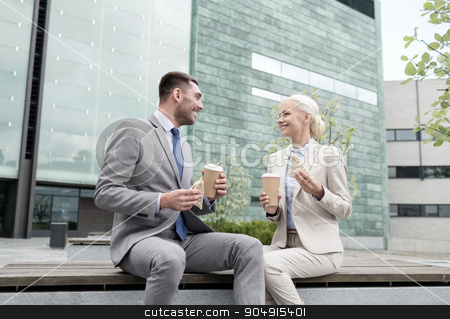 smiling businessmen with paper cups outdoors stock photo, business, partnership, food, drinks and people concept - smiling businessmen with paper cups standing over office building by Syda Productions