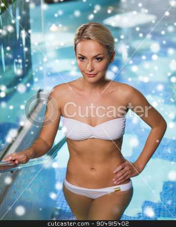 happy woman raising upstairs in swimming pool stock photo, people, beauty, spa, healthy lifestyle and relaxation concept - beautiful young woman in bikini swimsuit raising upstairs in swimming pool with snow effect by Syda Productions