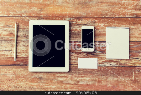 close up of notebook, tablet pc and smartphone stock photo, business, education, objects and technology concept - close up of notebook, tablet pc computer and smartphone on table by Syda Productions