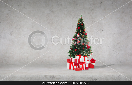 christmas tree with gifts over concrete wall stock photo, celebration, winter holidays and advertisement concept - christmas tree with gifts and santa hat over concrete wall background by Syda Productions