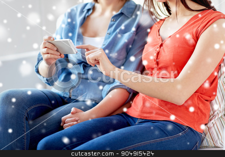 close up of lesbian couple with smartphone at home stock photo, people, homosexuality, same-sex marriage, gay and love concept - close up of happy lesbian couple with smartphone at home over snow effect by Syda Productions